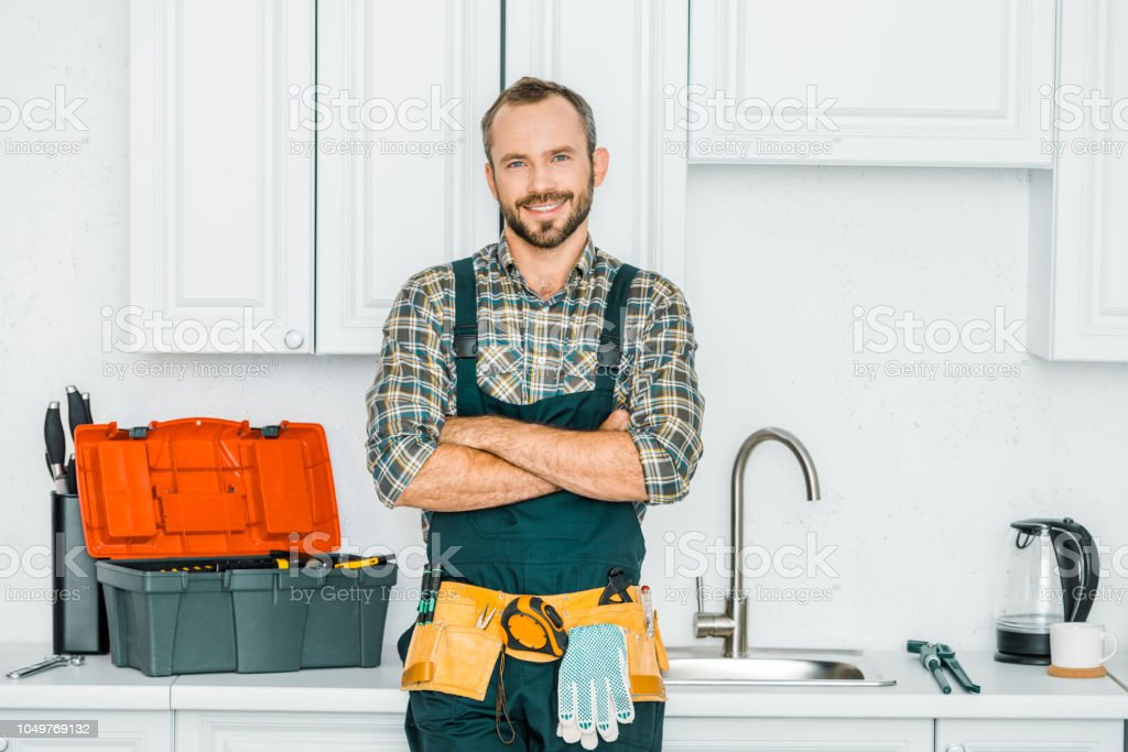 smiling handsome plumber standing with crossed arms and looking at camera in kitchen stock photo