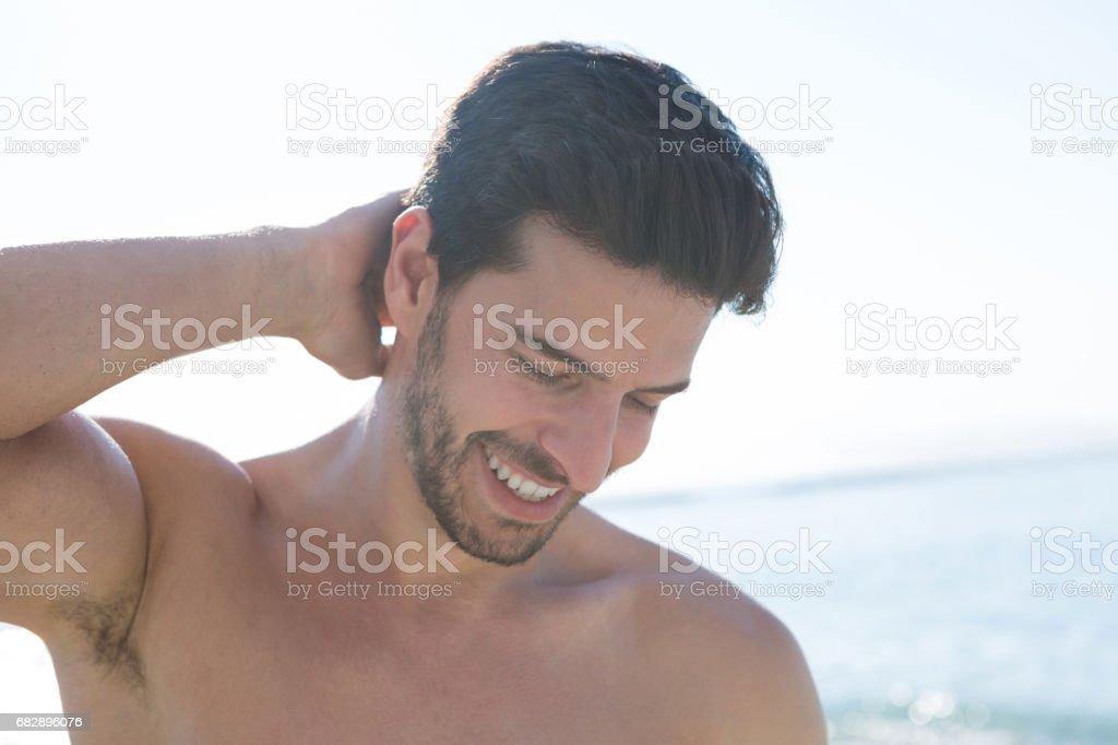 Lächeln auf den Lippen schöner nackter Oberkörper Mann am Strand Lizenzfreies stock-foto