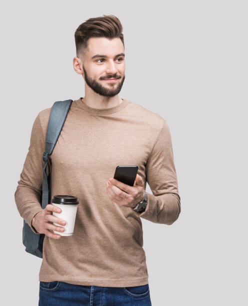 Smiling handsome student man using smartphone stock photo