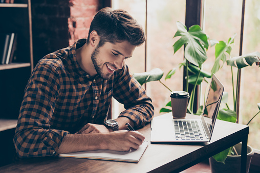 istock Smiling handsome student working with laptop and making notes 944652612