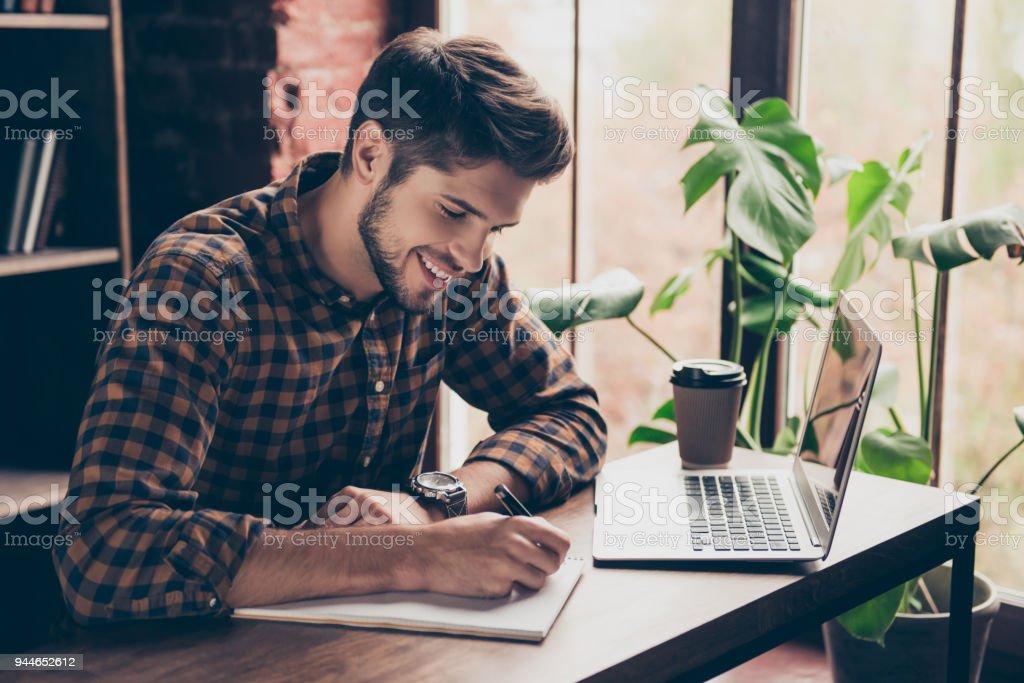 Estudiante guapo sonriente trabajando con el portátil y hacer notas - foto de stock