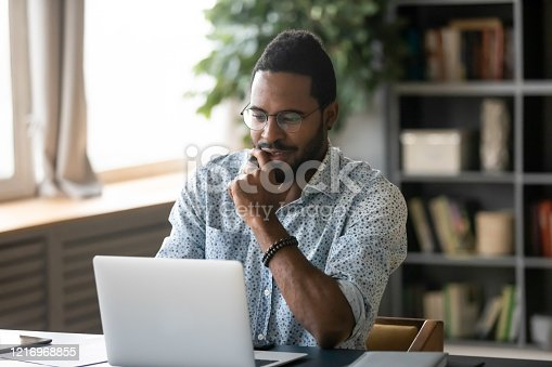 1053499704 istock photo Smiling handsome young african american guy looking at computer screen. 1216968855
