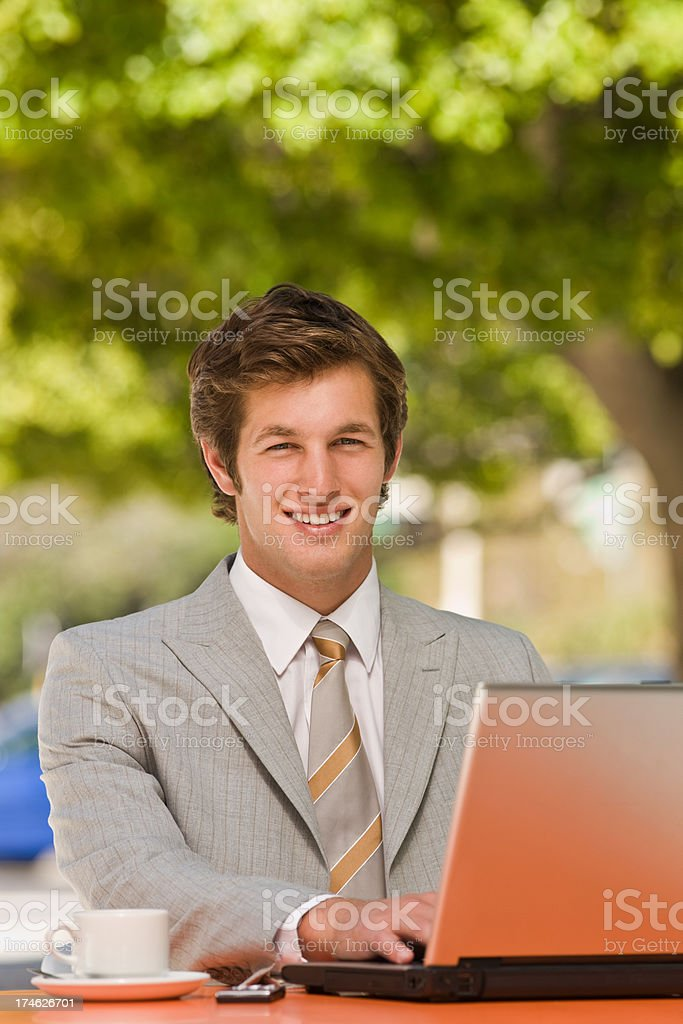 Smiling handsome young businessman using laptop royalty-free stock photo