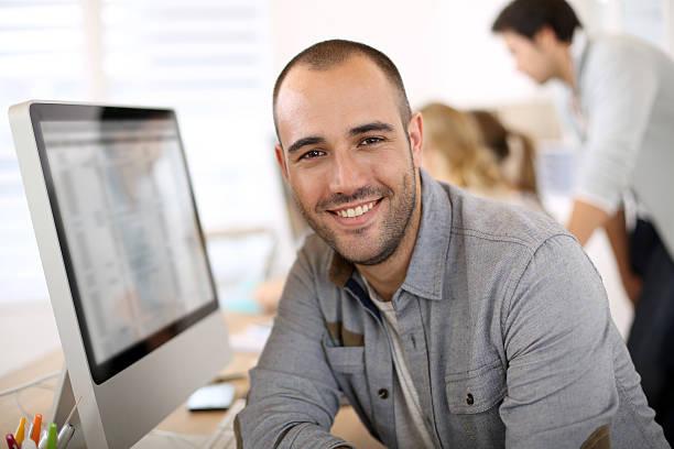 Lächelnd hübscher junger Mann im Büro – Foto
