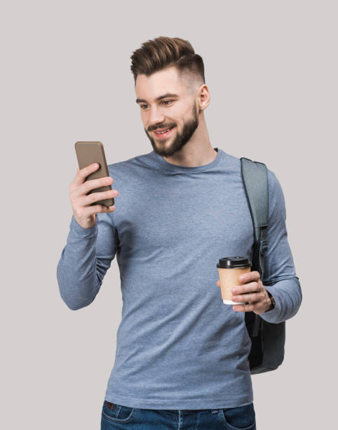 Smiling handsome young man using smartphone stock photo