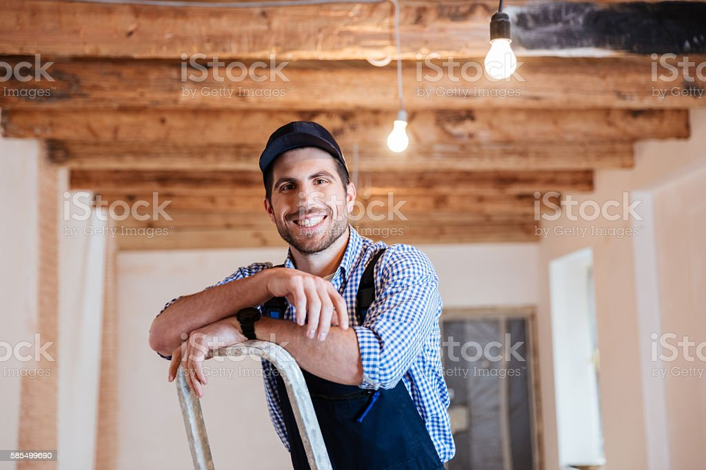 Smiling handyman standing on the ladder stock photo