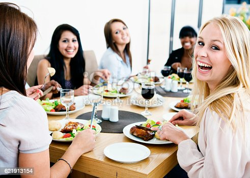 A happy group of young girlfriends or colleagues gather round a dining table to enjoy a meal and some fun together.