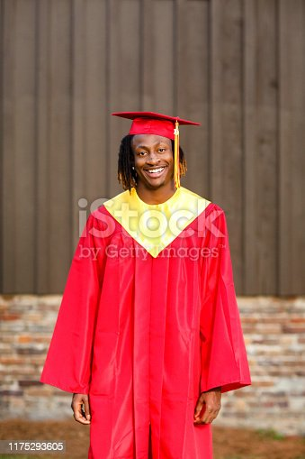 istock Smiling happy African-American Teen Teenager male Man outside against a brown wall in his red and gold graduation gown 1175293605