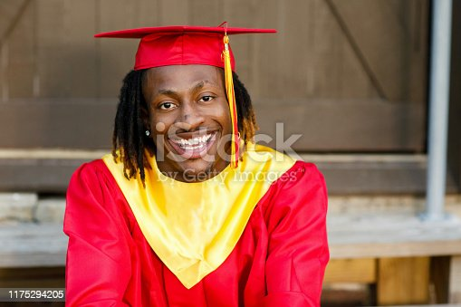 istock Smiling happy African-American Teen Teenager male Man outside against a brown wall in his red and gold graduation gown 1175294205
