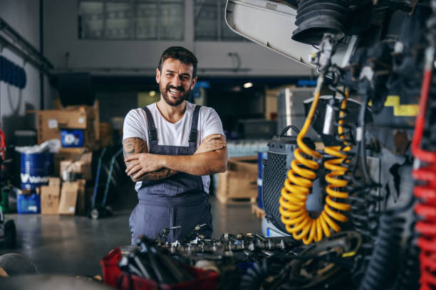 Smiling happy bearded tattooed worker in overalls standing next to truck with arms crossed. stock photo