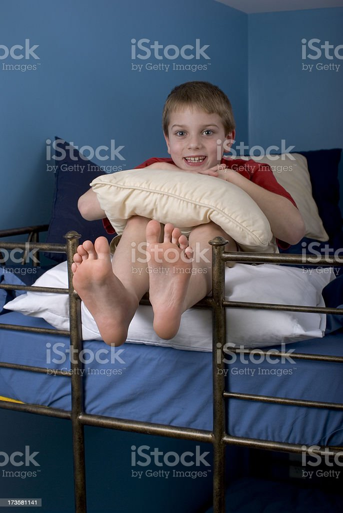 Smiling Happy Boy On Bunk Bed Feet Hanging Over royalty-free stock photo