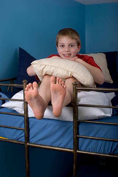 lächelnd fröhliche junge auf etagenbett füße hängen über - etagenbett weiss stock-fotos und bilder