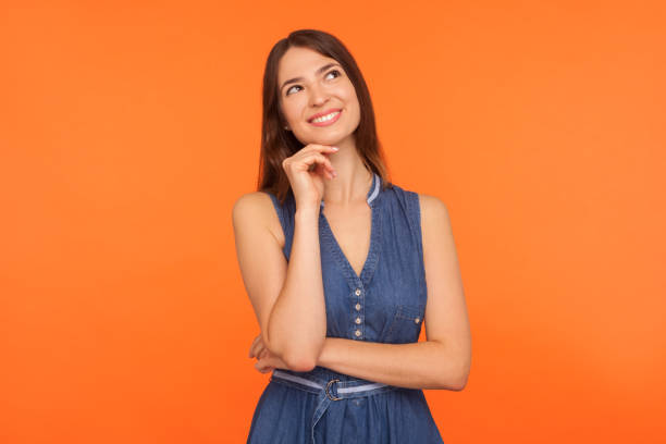 Smiling happy brunette woman in denim dress looking up with dreamy peaceful expression stock photo