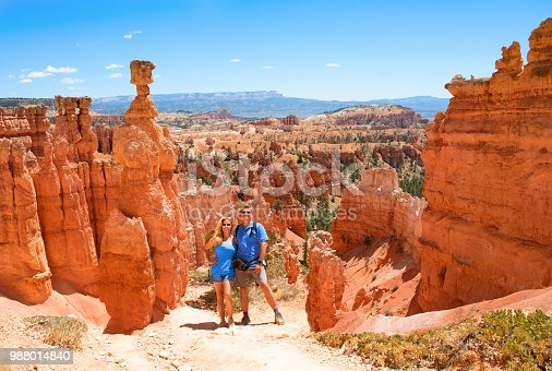 People enjoying summer hiking trip. Smiling happy  couple embracing on vacation in the red mountains. Bryce Canyon National Park, Utah, USA