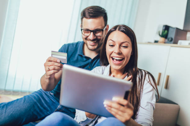 Smiling happy couple with tablet pc computer and credit or bank card shopping online at home stock photo