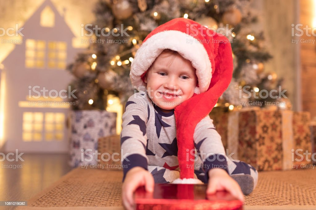 b950f9d1cc9a2 Smiling happy cute child in Santa red hat holding Christmas gift in hand  near a Christmas tree - Stock image .
