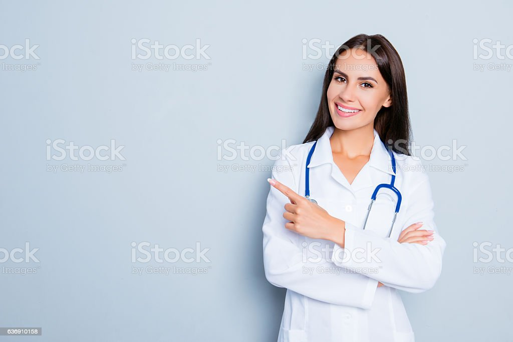 Smiling happy doctor pointing with finger on blue background ストックフォト