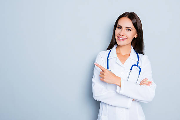 smiling happy doctor pointing with finger on blue background - docteur photos et images de collection