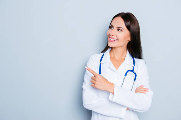 Smiling happy doctor pointing with finger on blue background stock photo