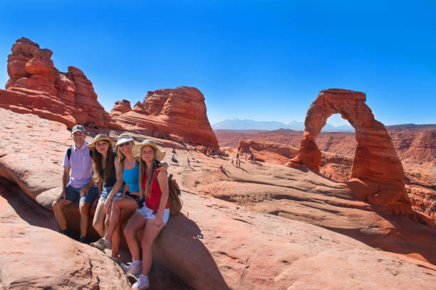 Smiling happy family on summer vacation hiking trip. Smiling happy family on vacation hiking trip. People relaxing  on top of  mountain next to Delicate Arch  enjoying time together. Arches National Park, Utah, USA delicate arch stock pictures, royalty-free photos & images