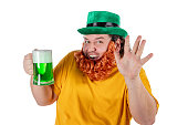 A smiling happy fat man in a leprechaun hat with green beer. He celebrates St. Patrick