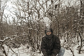 Smiling happy joyful Portrait of a Man wearing a black pullover jacket enjoying first snow playing and throwing snowball in air. Enjoy Snowing day view in winter. Rural village Jammu and Kashmir India