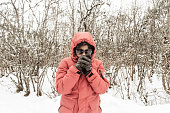 Smiling happy joyful Portrait of a Woman wearing a red pullover jacket and gloves enjoying first snow while shakes off snowball. Enjoy Snowing day view in winter. Rural village Jammu and Kashmir India