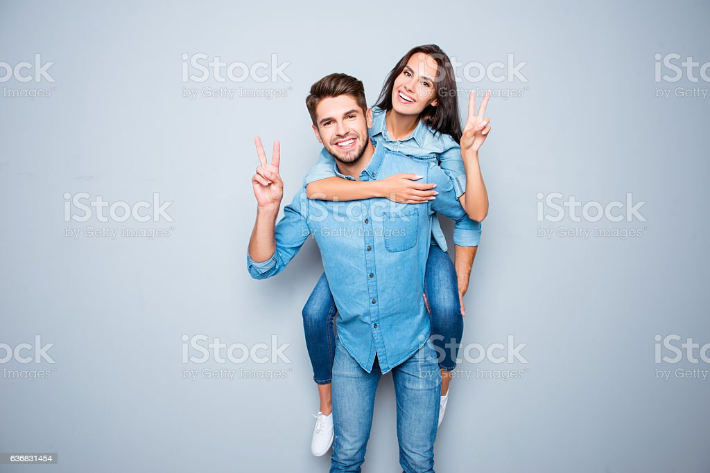 Smiling happy man piggybacking his girlfriend and gesturing v-siпт stock photo