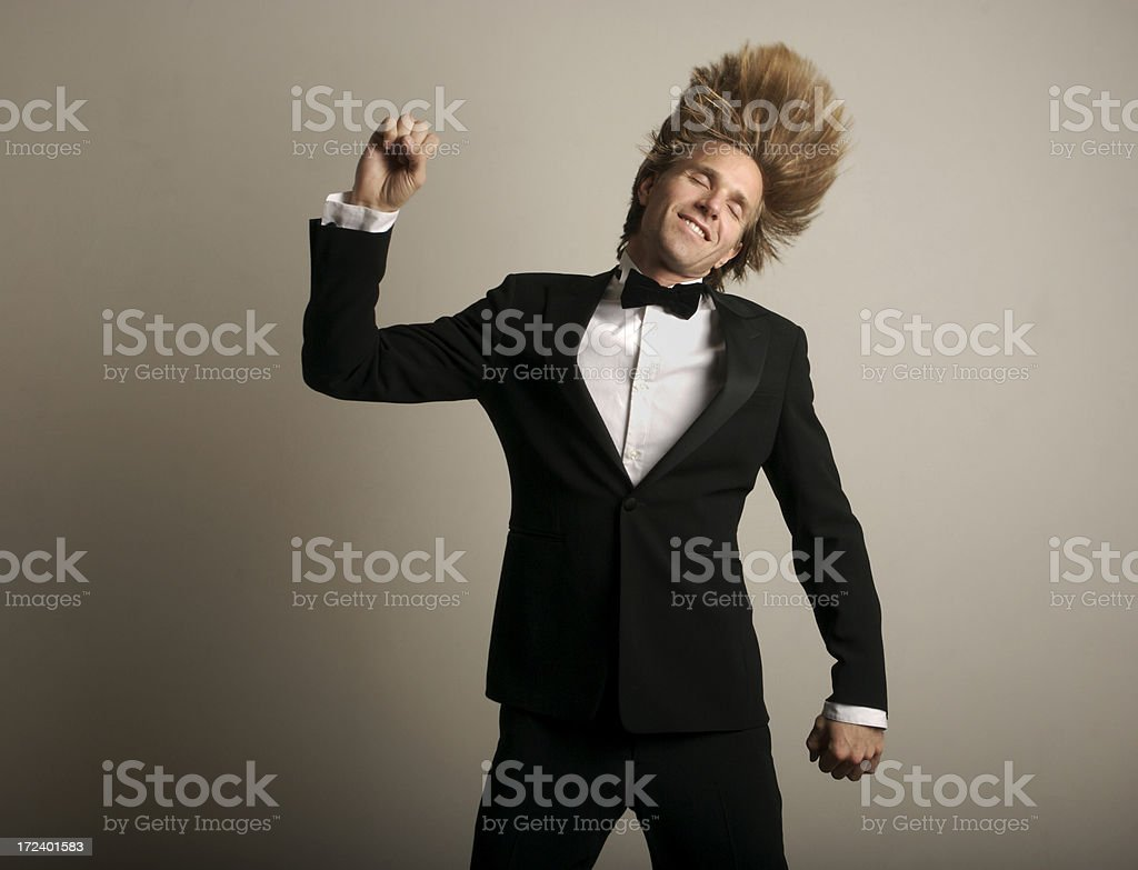 Smiling Happy Man with Long Blond Hair Dancing in Tuxedo stock photo