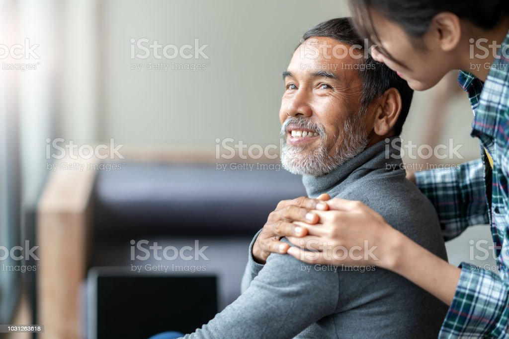 Smiling happy older asian father with stylish short beard touching daughter's hand on shoulder looking and talking together with love and care. Family relationship with bond and care concept. stock photo