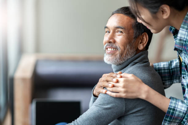smiling happy older asian father with stylish short beard touching daughter's hand on shoulder looking and talking together with love and care. family relationship with bond and care concept. - accudire foto e immagini stock