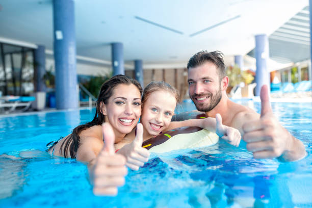 Smiling happy people in the swimming pool stock photo