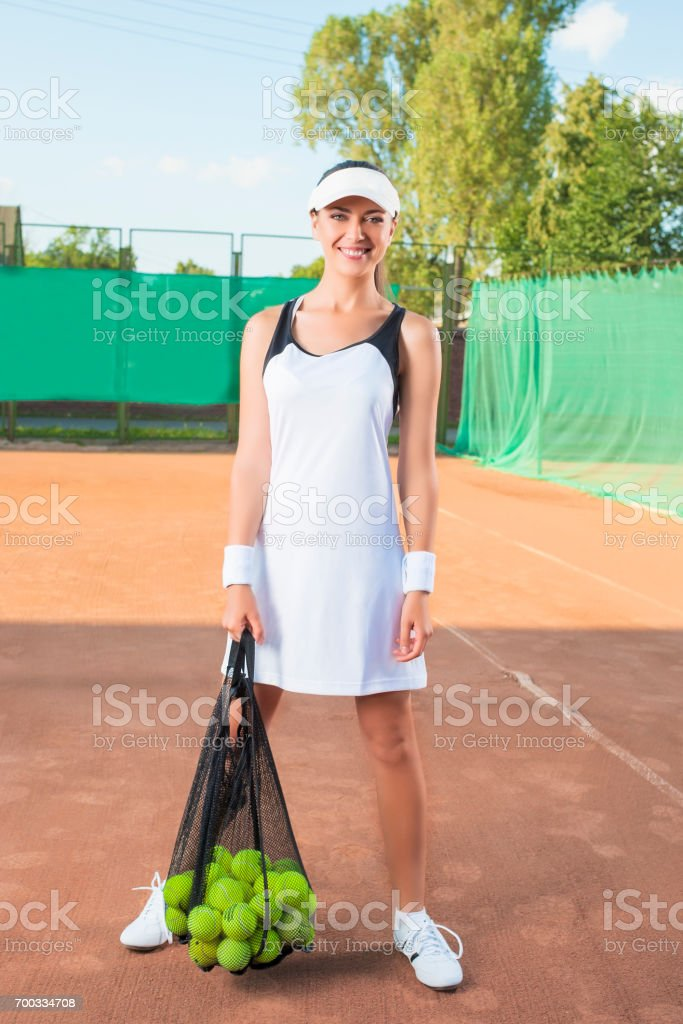 Smiling Happy Tennis Woman At Court with Mesh Bag Full of Balls....