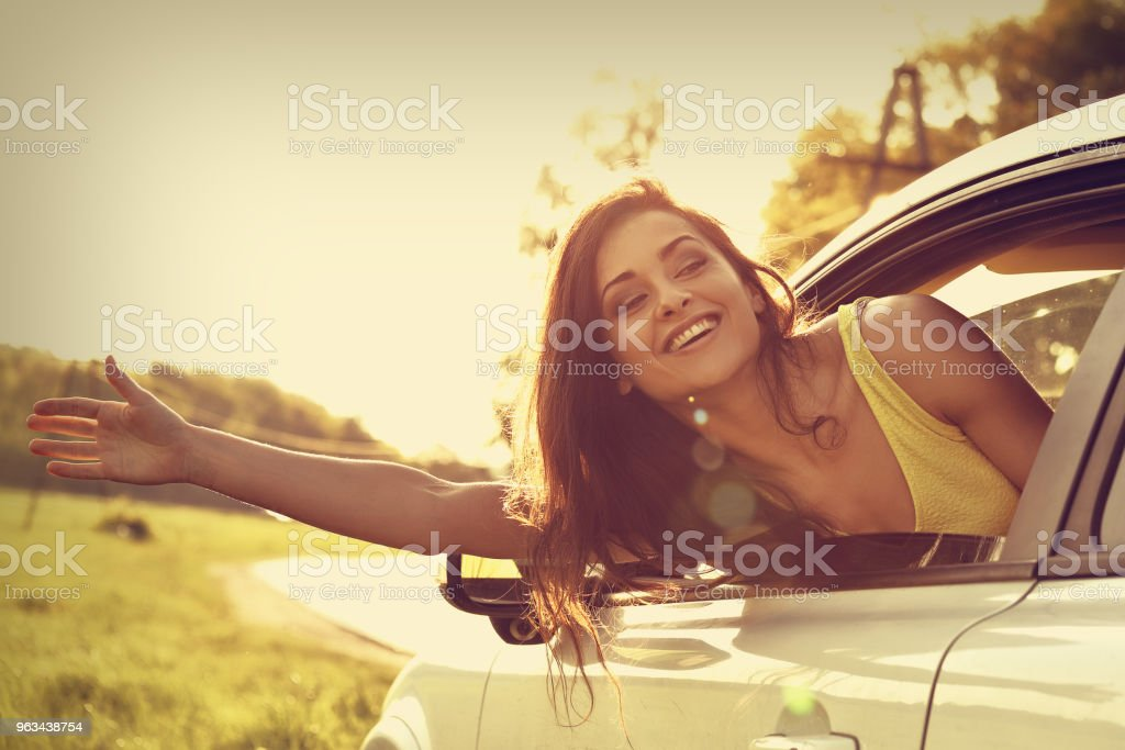 Smiling happy traveling young woman looking from the new car window and holding the hand towards the fress air on summer bright nature background. Toned closeup vintage portrait - Zbiór zdjęć royalty-free (Czynność)