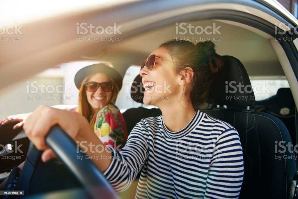 Smiling happy woman giving her friend a lift stock photo