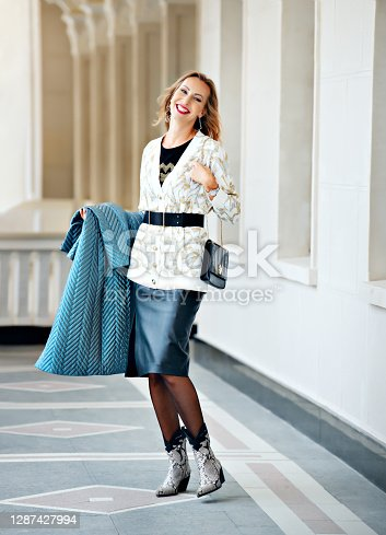Fashionable image: a girl model in a long black leather skirt, cowboy boots, with a black handbag, in a warm white elegant blouse with a black leather wide belt. A woman holds a warm blue coat in her hands.