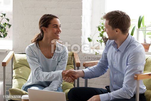 istock Smiling happy woman shaking hand of confident businessman 1124743209