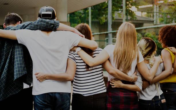 uśmiechnięty szczęśliwy młody dorosły przyjaciele ramiona wokół ramienia na zewnątrz przyjaźń i połączenie koncepcji - atmosfera wydarzenia zdjęcia i obrazy z banku zdjęć