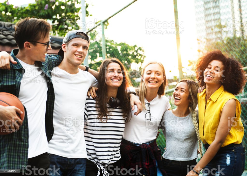 Smiling happy young adult friends arms around shoulder outdoors friendship and connection concept stock photo