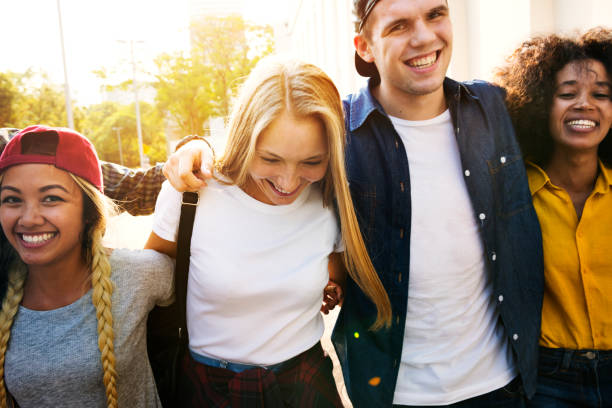Smiling happy young adult friends arms around shoulder walking outdoors Smiling happy young adult friends arms around shoulder walking outdoors generation z stock pictures, royalty-free photos & images