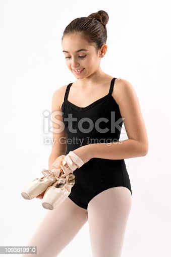 Smiling happy young ballerina with her long hair in a bun standing holding her pink on pointe ballet shoes in her hands in a three quarter pose isolated on white