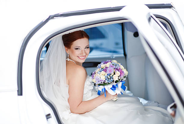 Smiling happy young bride sitting in white limo. stock photo