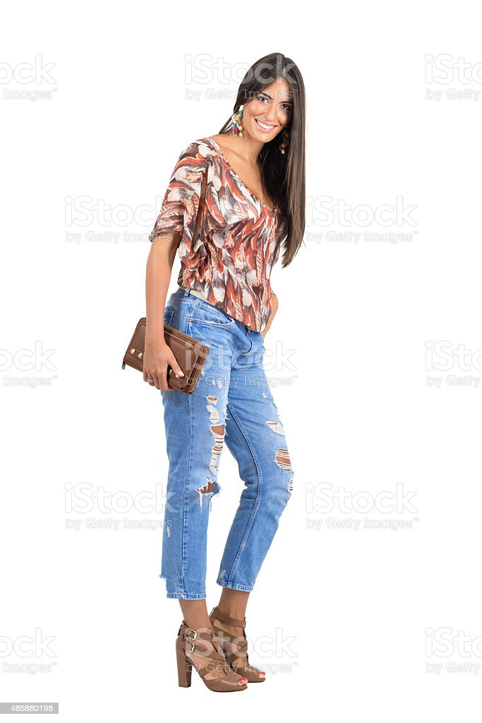 Smiling happy young Latin woman holding purse looking at camera stock photo