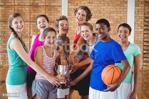 istock Smiling high school kids holding trophy in basketball court 676150476