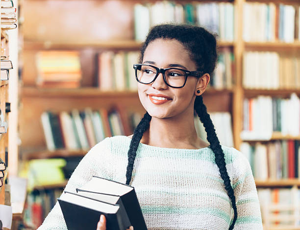 Smiling high school student holding books at library stock photo