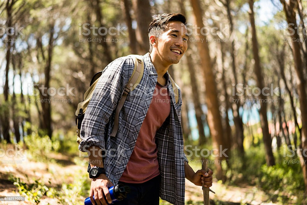 Smiling hiker holding stick and water bottle – Foto