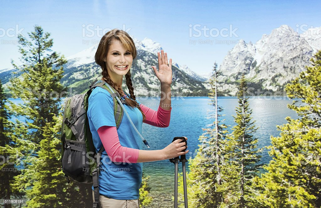 Smiling hiker in front of rural scene & waving hand stock photo