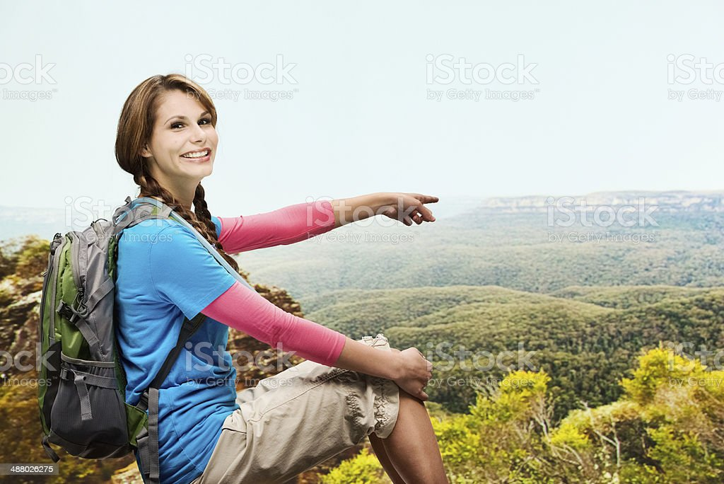 Smiling hiker sitting and pointing away stock photo