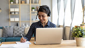 istock Smiling hindu woman studying online, sitting at desk with computer. 1257836750