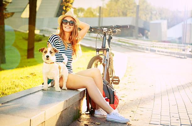 smiling hipster girl with her dog in summer city - sommer teenagermode stock-fotos und bilder